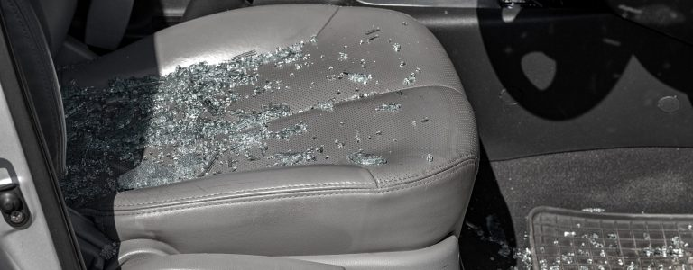 Criminal incident. Hacking a car. Broken driver's side window of car. Thieves smashed window of car with fragments inside, glass was scattered throughout. Crime - broken window and theft belongings