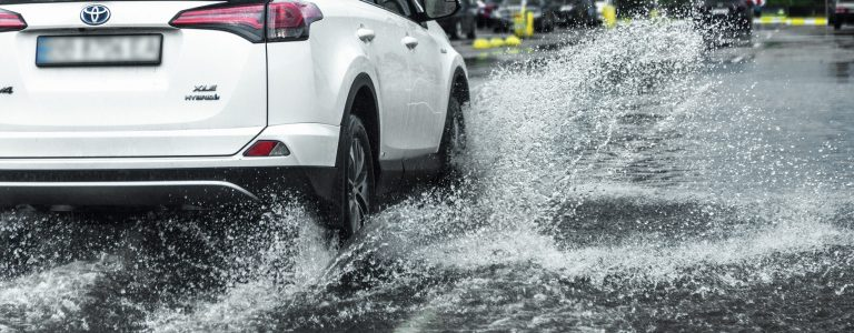 Odessa, Ukraine - August 9, 2019: driving car on flooded road during flood caused by torrential rains. Cars float on water, flooding streets. Splash on the car. Flooded city road with a large puddle