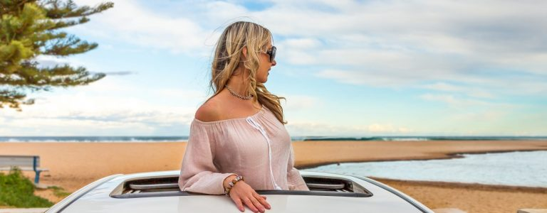 Rolad trip summer beach vibes.  Woman stand in the sunroof of her car by the beach.