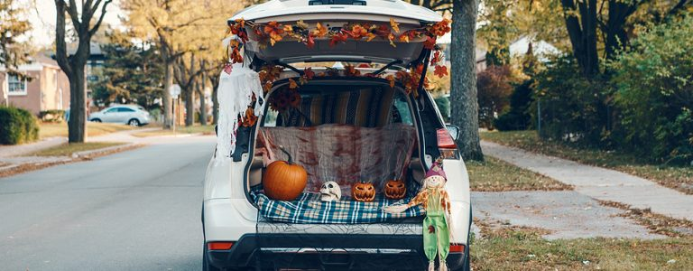 Trick o trunk. White car trunk decorated for Halloween. Autumn fall decor with red pumpkins and yellow leaves for traditional October holiday outdoor. Social distance and alternative safe celebration